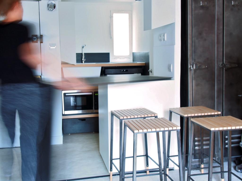 cuisine sur mesure ingénieuse dans un petit appartement parisien, une solution sur mesure originale créé, dessiné et fabriqué par le studio toulousain superstrate, matériaux, acier noir, laque blanc mat et corian.
