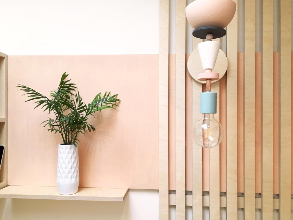 meuble design minimal, panneau mural rose pale et latté de bois bouleau clair, luminaire design d'inspiration memphis, forme géométrique et couleur pastel rose et bleu