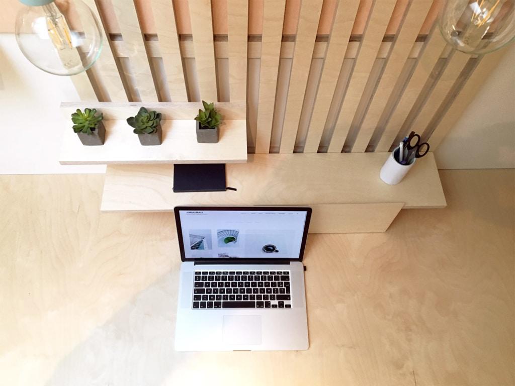 bureau en angle design sur-mesure en bois de bouleau clair, latté de bois clair et rangement fermé en stratifié blanc et tapisserie fleurie, luminaire design d'inspiration memphis, forme géométrique et couleur pastel