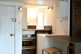 cuisine originale dessiné pour un petit espace parisien, le mobilier de cuisine est sur mesure pour optimiser l'espace réduit de ce lieu. Une cuisine fonctionnelle en bois d'érable, Corian et acier noir et blanc esprit industriel chic réalisé par le studio de design et fabrication superstrate à Paris